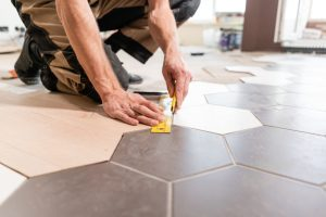 Male,Worker,Makes,Measurements,And,Installing,New,Wooden,Laminate,Flooring.